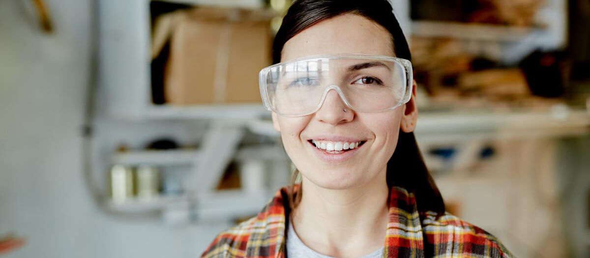 woman in wood shop wearing protective glasses