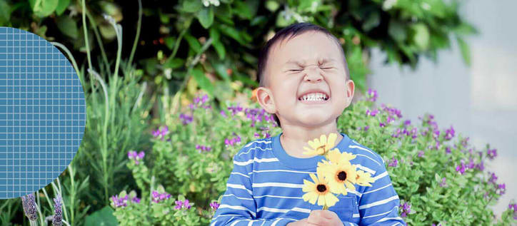child smiling holding flowers in front of plants