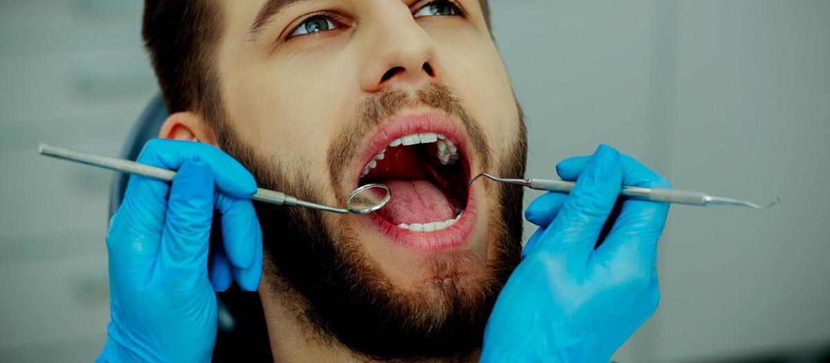 man getting dental cleaning on his teeth