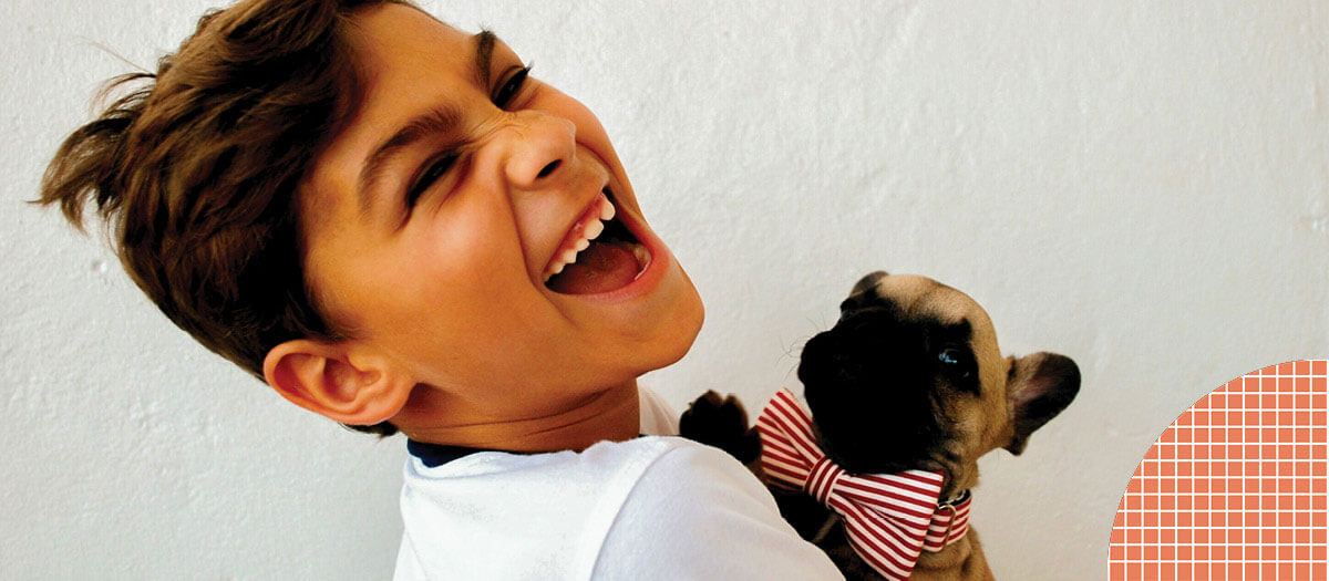 Young boy carrying puppy