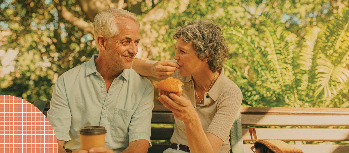 Senior couple eating breakfast on park bench