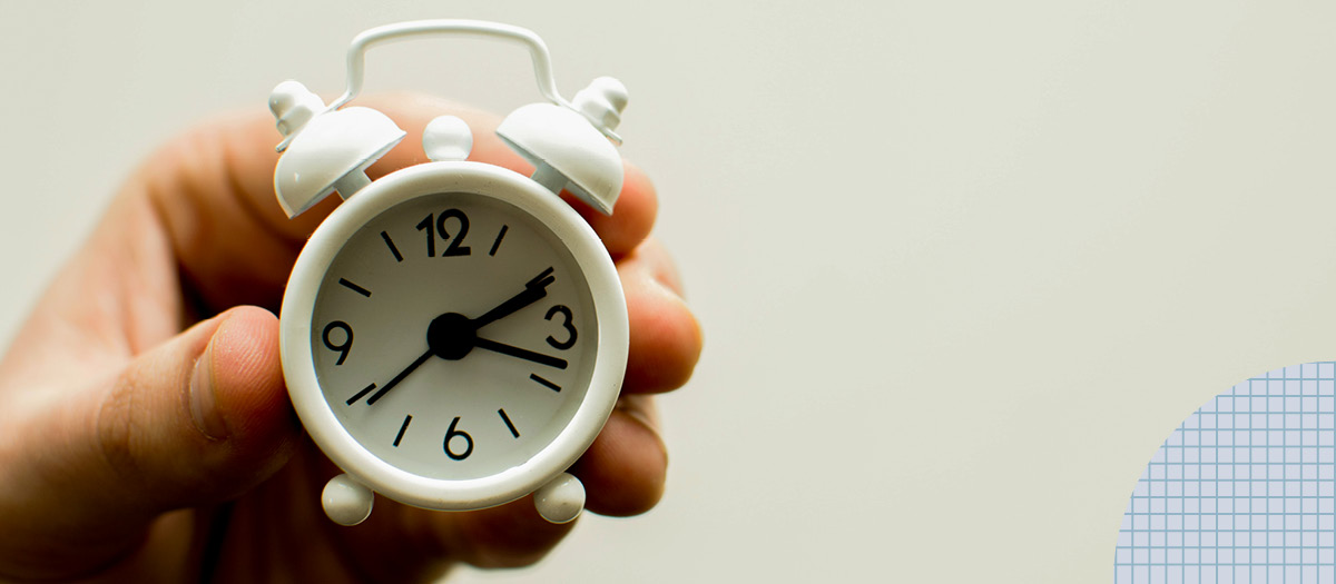 Hand holding up small clock waiting