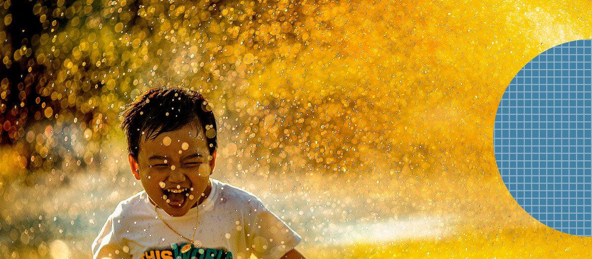 Kid smiling running through sprinkler
