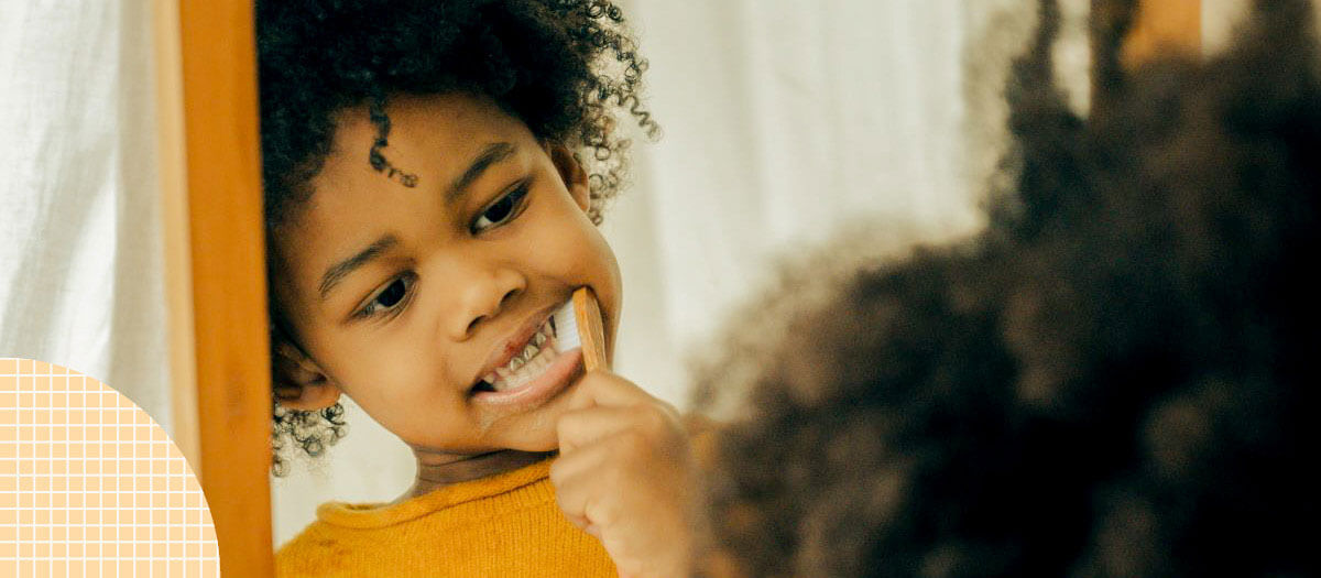 Child brushing teeth in mirror