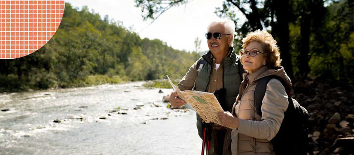 Senior couple looking at map near river