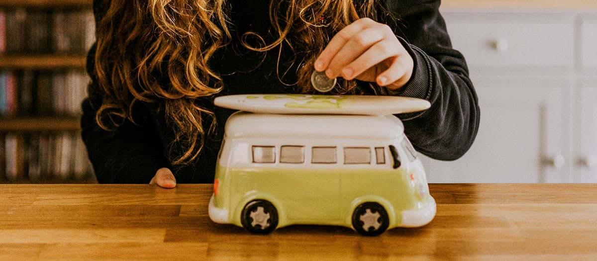 person putting coin in van-shaped piggy bank