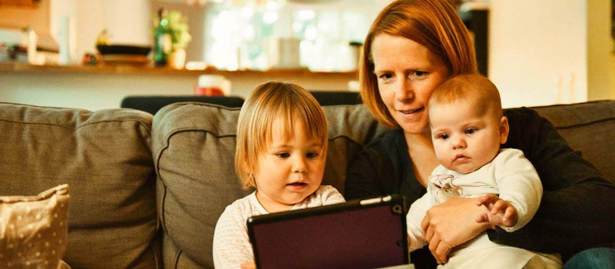 Mom and two young kids playing on an iPad