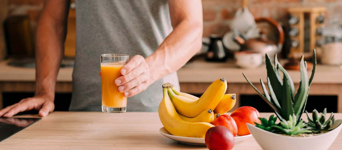 Man drinking orange juice in his kitchen