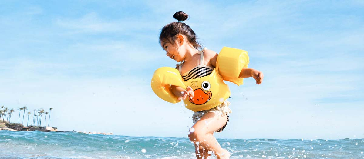 Girl playing in the water at the beach with floaties
