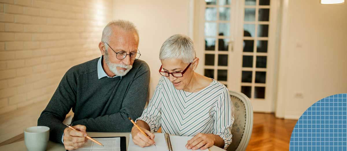 Senior couple going over paperwork in dining room