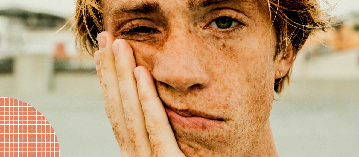 Freckled boy holding face in pain