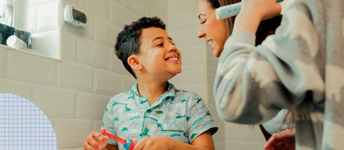 Boy brushing teeth with his mom in bathroom