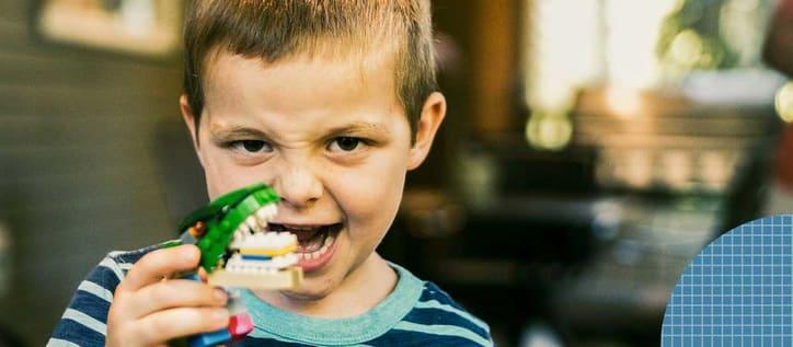 Kid holding up building blog teeth