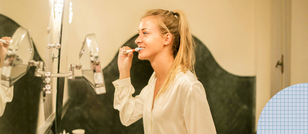 Girl brushing her teeth in front of mirror