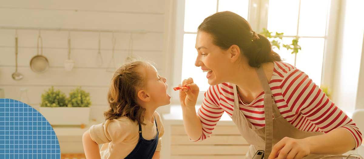 Woman feeding young girl in apron
