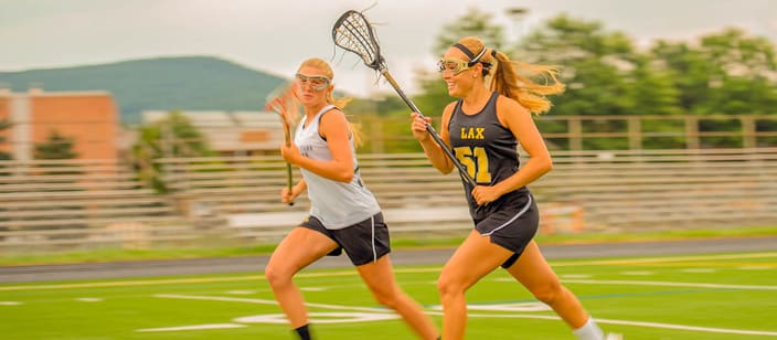 Two teenage girls playing high school lacrosse