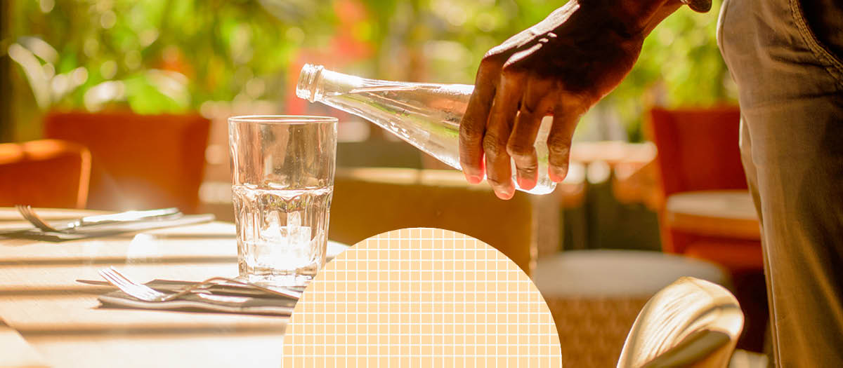 waiter pouring a glass of sparkling water at table