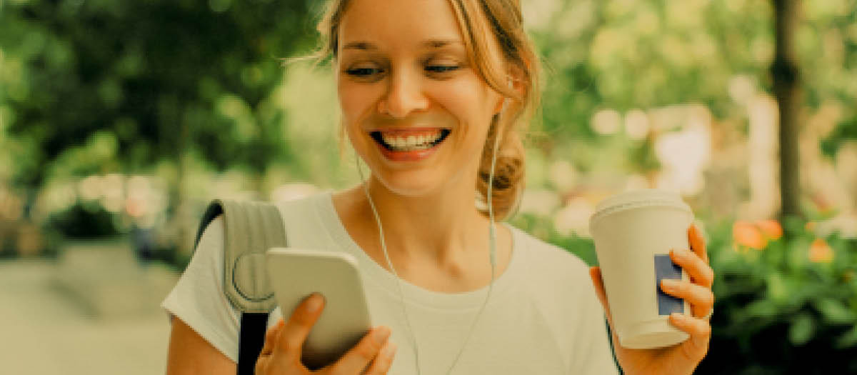 Girl with headphones on looking at phone and holding a coffee