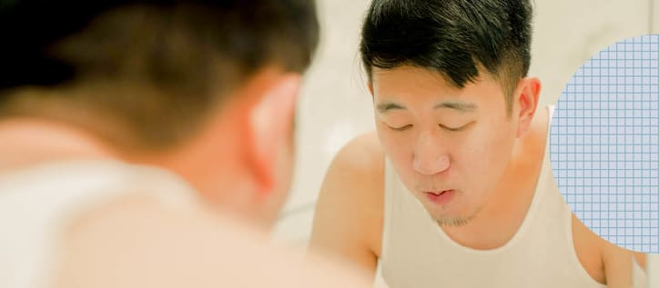 Man rinsing mouth out near kitchen sink