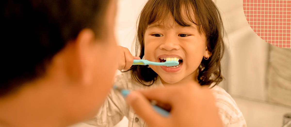 Small girl brushing her teeth while looking at her dad