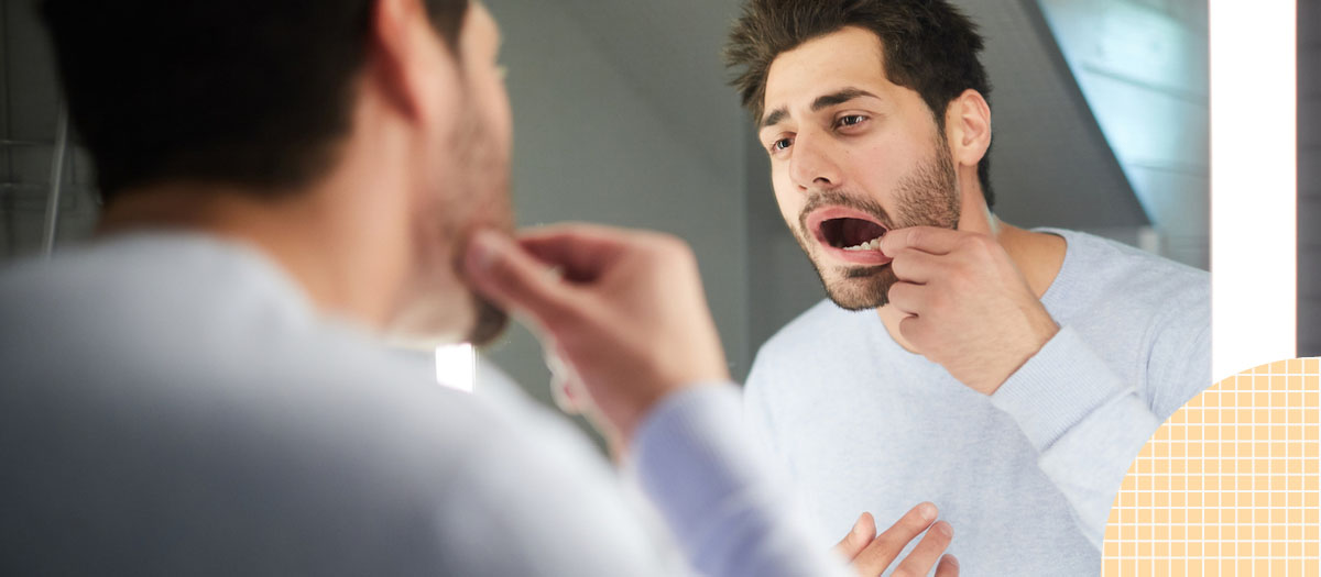 Man checking out his teeth in the mirror