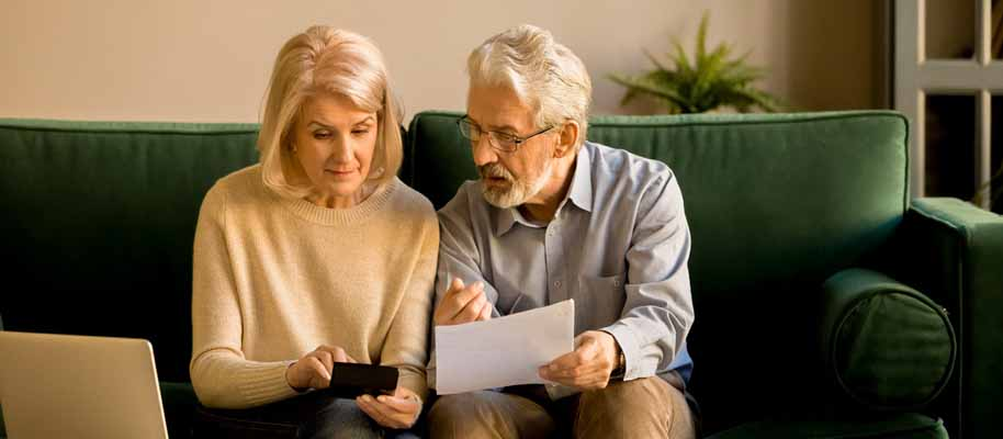 Older couple reviewing bills on couch